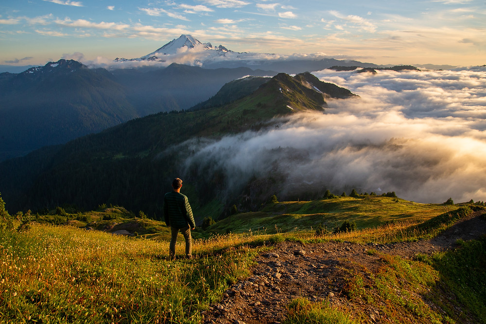 A hiker standing above the clouds on Yellow Aster Butte with a view of Mount Baker in the Mount Baker Wilderness in Washington.