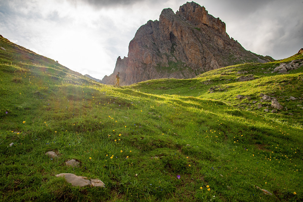 A hiker in alpine meadow under a mountain in the Alps of France.