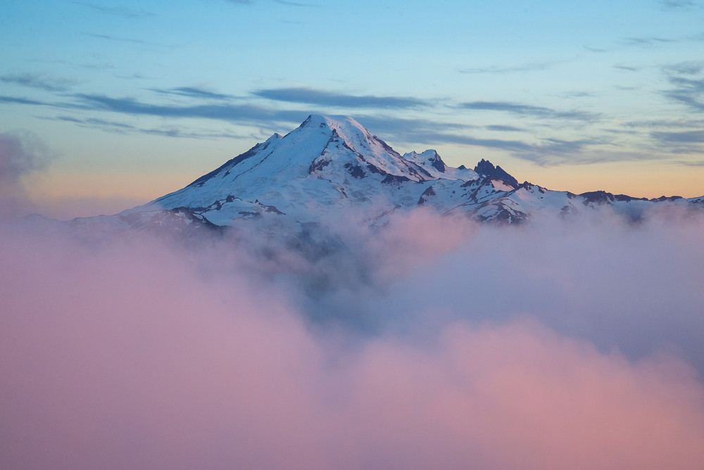 Mount Baker rises above the clouds at sunset in the Mount Baker Wilderness in Washington.