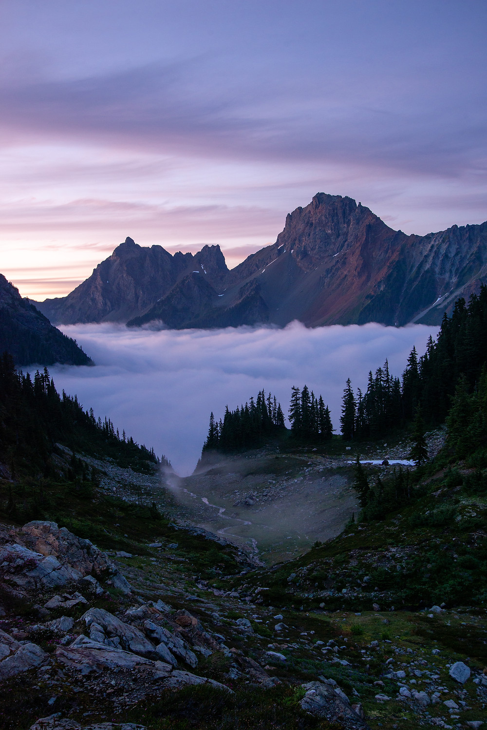 Clouds fill the valley below American Border Peak and Canadian Border Peak in the Mount Baker Wilderness in Washington.