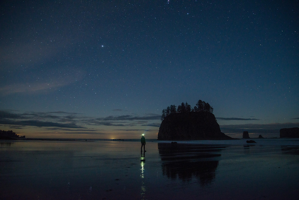 Hiker on the beach at night under stars on Second Beach in Olympic National Park in Washington.