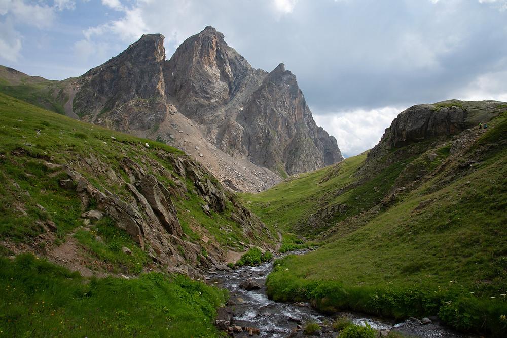 A stream cuts through a valley beneath big limestone peaks.