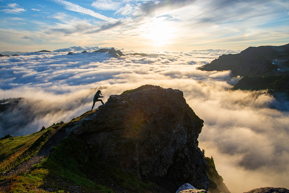 A hiker scrambles up a ridge above the clouds in the Mount Baker Wilderness in Washington.