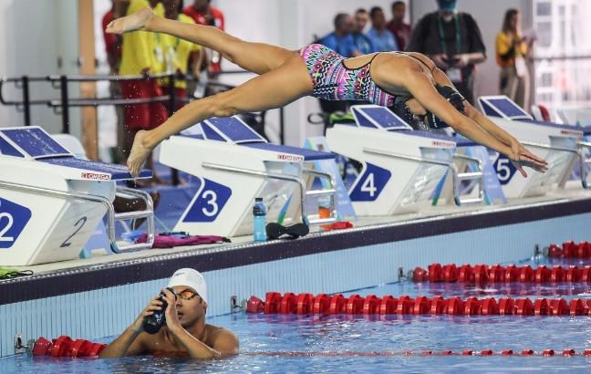 Yusra Mardini se zambulle al agua mientras Rami Anis se hidrata con agua en el Estadio Olímpico Acuático (Foto: Getty Images/Mario Tama)