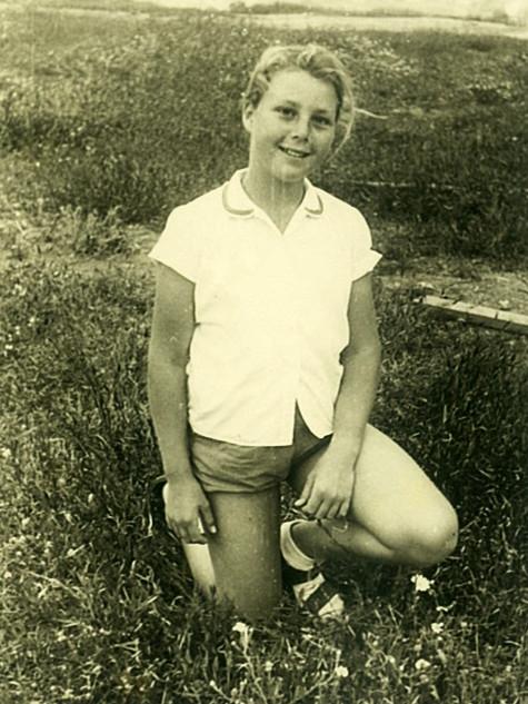 נעמי מנהיימר (לימים צעירי) בבגדי חג הפסח החדשים, ברקע שדה השיבולים של קיבוץ גליל ים, שנות החמישים