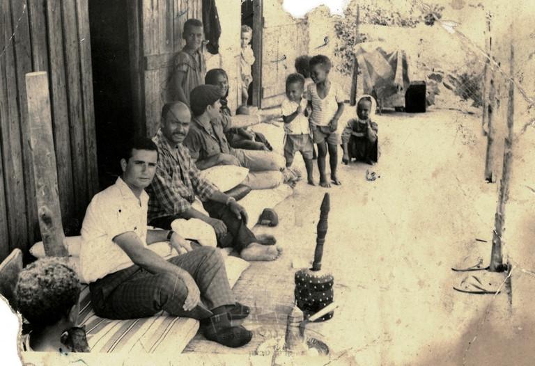 """משפחת דאהוד ושרה מארחת על כוס קפה (""""פנגאל אהווה"""") בפתח צריף העץ בחילף, בסמת טבעון, סאלח בן השמונה עומד, נשען על גב הצריף, 1963 בערך."""