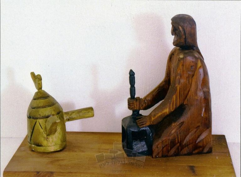 בדואי כותש גרגירי קפה במכתש (ג'ורן) להכנת הקהווה, פסל עץ  של האמן סלאח עליסאת