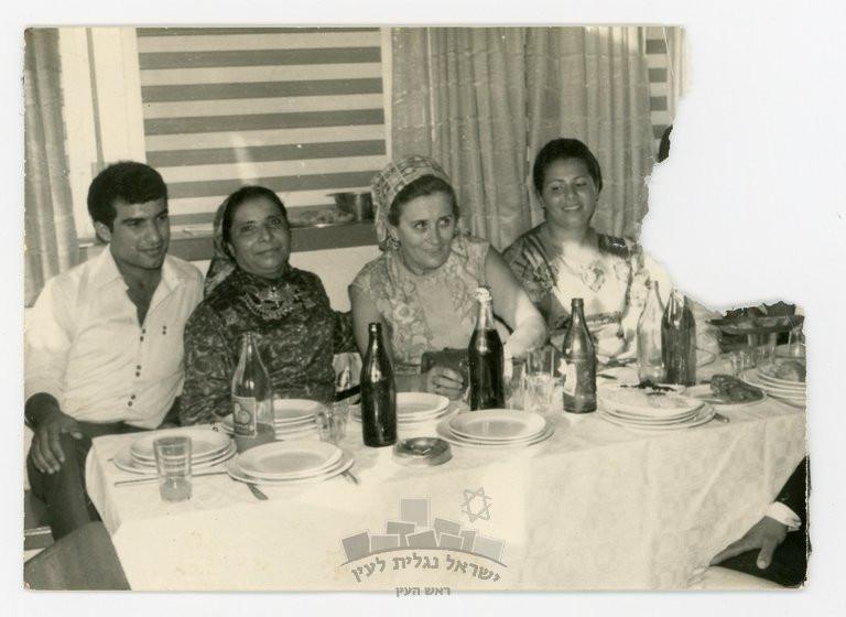 מימין לשמאל: שושנה ונה לבית קרואני (בתה של בדרה), רות דיין, בדרה קרואני ובנה עוזי, יושבים לשולחן ערוך במסגרת אירוע משפחתי של משפחת קראוני, 1967-9.