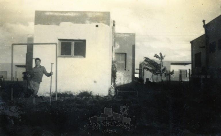 """בצילום נראה משה נוסוביצקי (נצר) ליד מתלה הכביסה בחצר ביתו בשכונת הפועלים אז""""ר בתל אביב, 1933"""