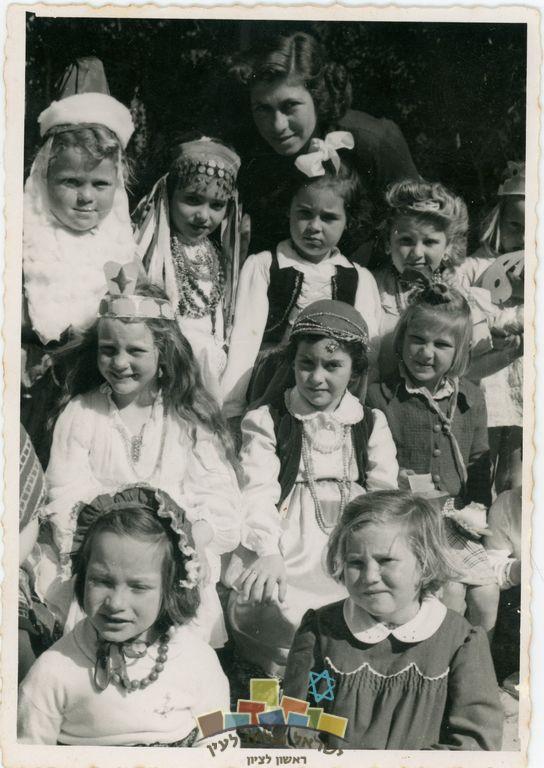 """ילדות בתחפושות פורים בגן הילדים העירוני ברחוב זד""""ל, ראשון לציון, 1949 נאוה קלס בת החמש מחופשת לצועניה בשורה האמצעית במרכז. מימינה צביה בקר, משמאלה רחל אלוי. בשורה העליונה, שנייה מימין עליזה אנגל, לידה מירה מלבסקי, רלי שינדלר. מאחור הגננת שרה מאירי."""