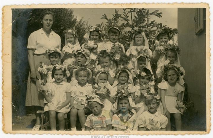 מרדכי (מוטי) פינקלשטיין [בשורה השניה עומד חמישי מימין] וילדי הגן בחגיגת שבועות עם הגננת, 1951, אלבום מרדכי (מוטי) פינקלשטיין – נורדיה