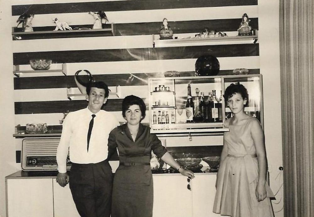 המזנון בסלון בית משפחת פשחצקי ברמת גן, 1964-5. מכשיר הרדיו משמאל, לידו אלכס פשחצקי עם בת דודתו שולמית דוד.בצד ימין של התמונה בתו של אלכס, חסידה.