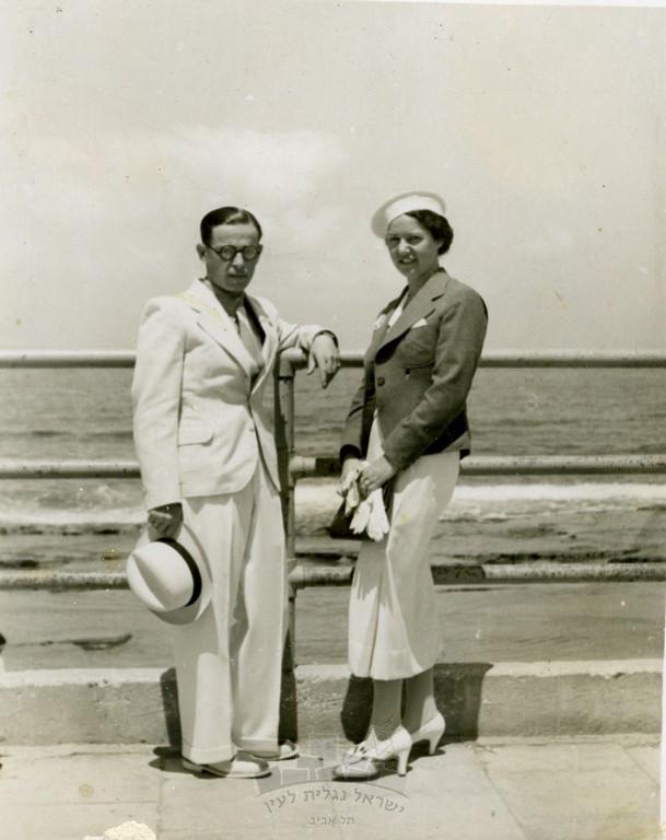 """מיכל תמרי ובעלה לעתיד מיכאל גרסטל, על רקע """"הברזלים"""" בטיילת, תל אביב, 1936"""