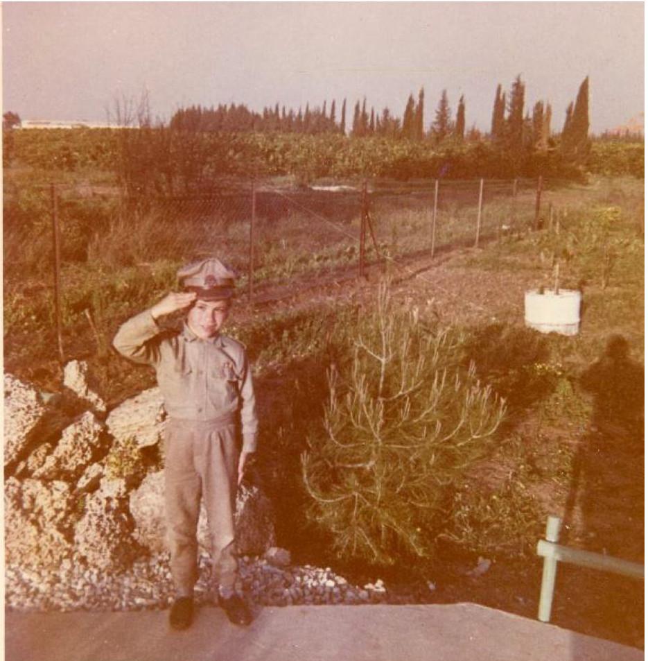אבי רובינשטיין מחופש לשוטר, בחצר ביתו במגדיאל סמוך לשתיל עץ האורן, 1965
