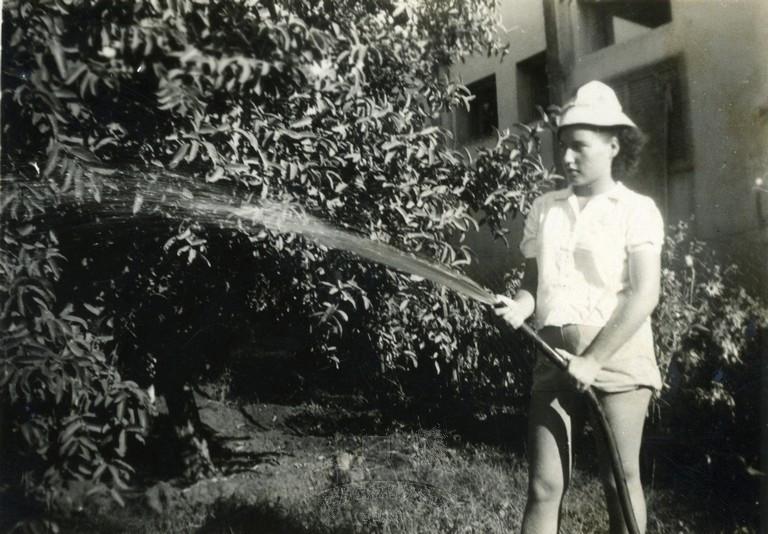 """רנה נוסוביצקי (נצר), לימים שפירא, משקה את גינת ביתה בשכונת הפועלים אז""""ר בתל אביב, 1945"""