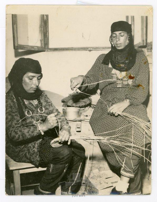 """""""בדרה (משמאל) וברדגושה קולעות סלים, 1953 בערך. בסיר נהגו למלא מים כדי לטבול את הצמחים ולרככם לפני הקליעה. ברדגושה, אמה ואחותה היו חלק מהנשים שאיגדה בדרה בשנות החמישים עבור רות דיין, בעלת """"משכית"""