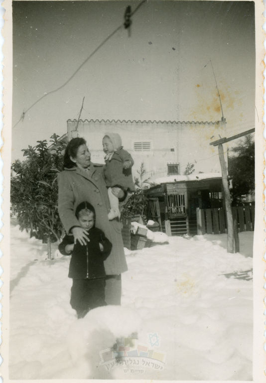 תמונת חנה נמרי עם בניה בחצר ביתה בק