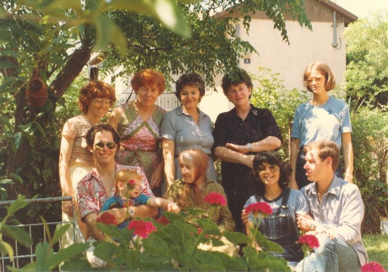 משפחת וייס בחצר ביתה בתל אביב, 1981. צילום: יעקב (יענקל'ה) וייס. מימין לשמאל, עומדים: מרב דני, בטי וייס, שולה דני, רבקה וייס (בשמלתה הפרחונית), אביבה וייס; יושבים: אמיר רוגל (לשעבר וייס), רחלי רוגל, חנה וייס (סבתו של אמיר), אחיו בועז והנין ארז.