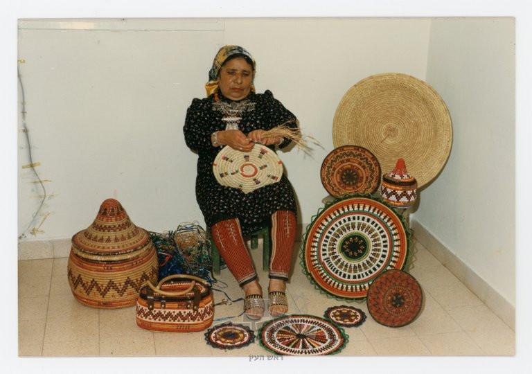 בדרה קרואני מדגימה את מלאכת הקליעה בביתה, ראש העין, 1984. מסביבה מבחר מיצירותיה: תחתיות לסירים, מגש לפיתות, קופסה לתכשיטים, תיק וסל לבגדים.