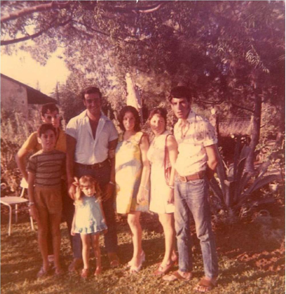 בחצר הבית במגדיאל, בצל עץ האורן, 1972. מימין: חנן (ג'וני), דינה, עליזה (ליזט) ובעלה ניסים בוזגלו (לימים בן אור), יוסי רובינשטיין, לפניו אבי רובינשטיין, הילדה גלית בן אור