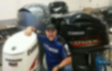 Owner Jeff Frahm standing next to an Evinrude, Yamaha, and Mercury outboard engine.