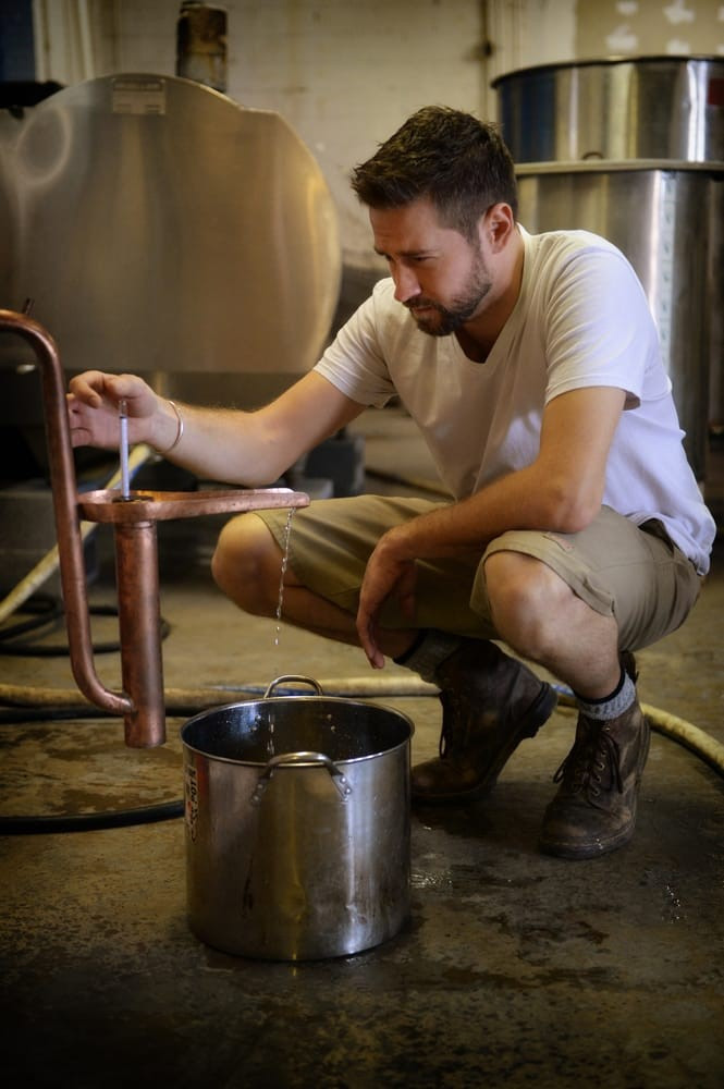 Tim, owner of Maggie's Farm, crouched while inspecting a still