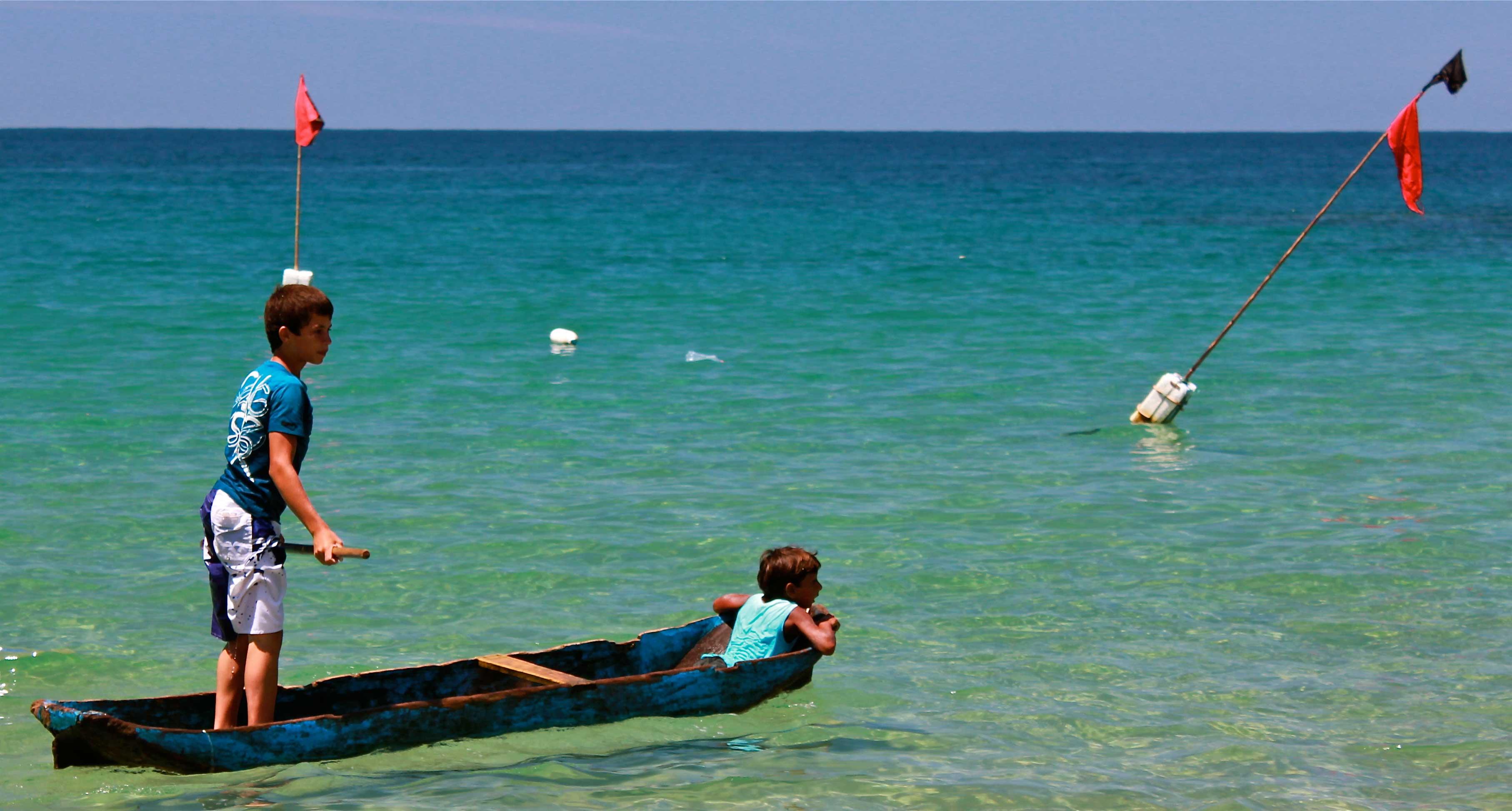 Crianças e a canoa caiçara