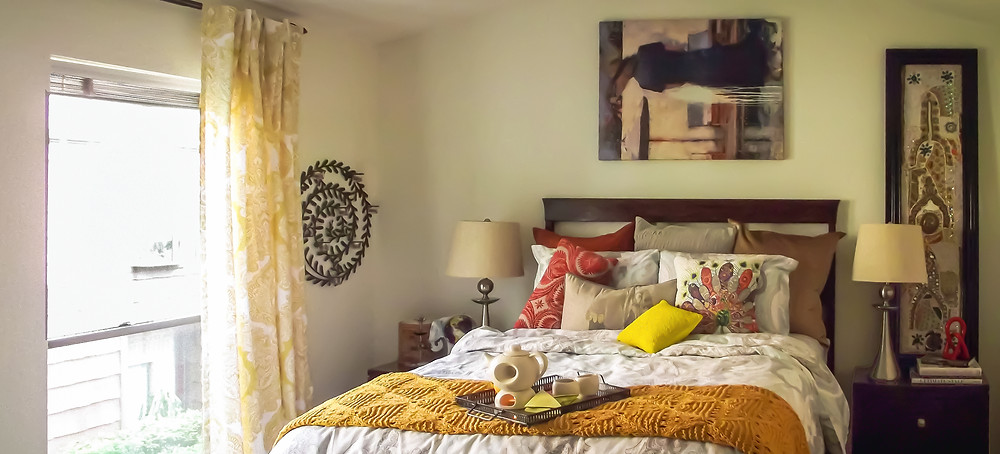 Eclectic master bedroom design featuring yellow throw, Chinese tea light tea set, Indian jewel embellished artwork, golden tones, damask gray and white bedding, and damask yellow curtain.