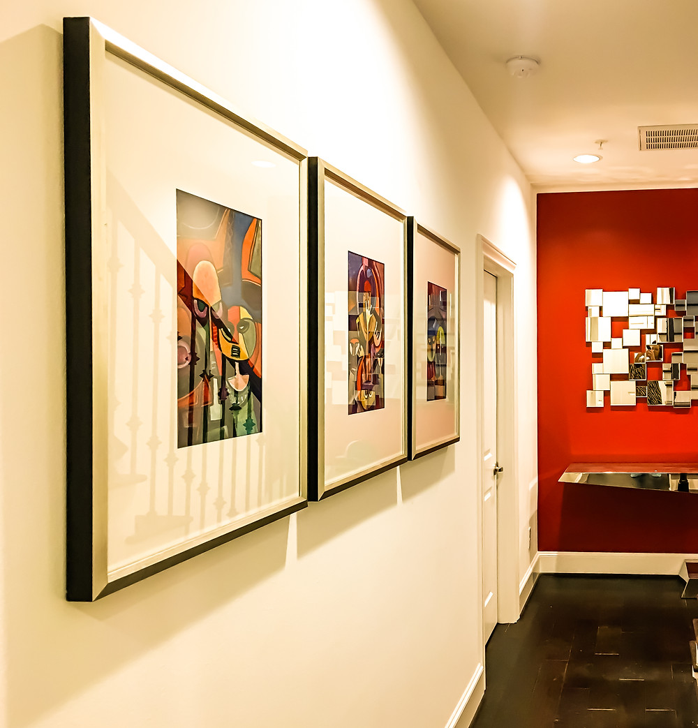 A series of black artwork hung on white walls adjacent to bold, red wall adorned by a artsy, conversational piece mirror hung above a chrome cool-shaped console table