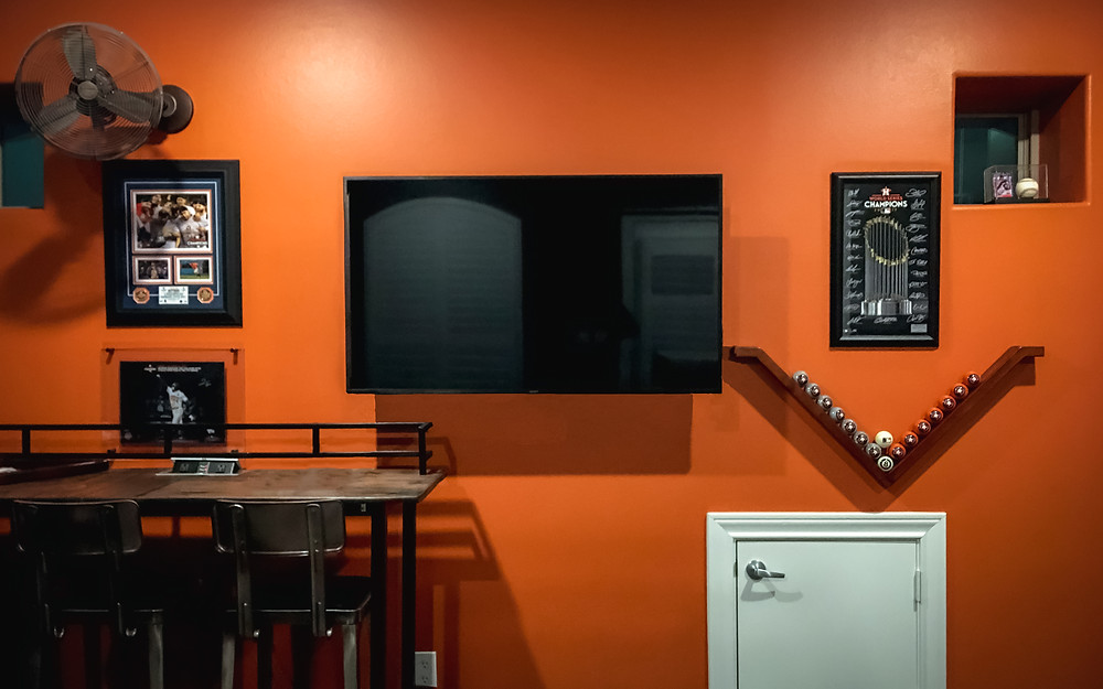 Bold orange wall adorned by Astros memorabilia, bronze wall fan, walnut wood pub table, steel silver leather black upholstered barstools, and Astros billiard balls