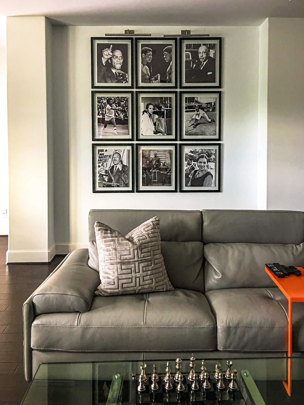 Gallery Wall of Important Black Persons on White Wall, Under Burnished Steel Picture Light, Facing Warm Gray Leather Sectional