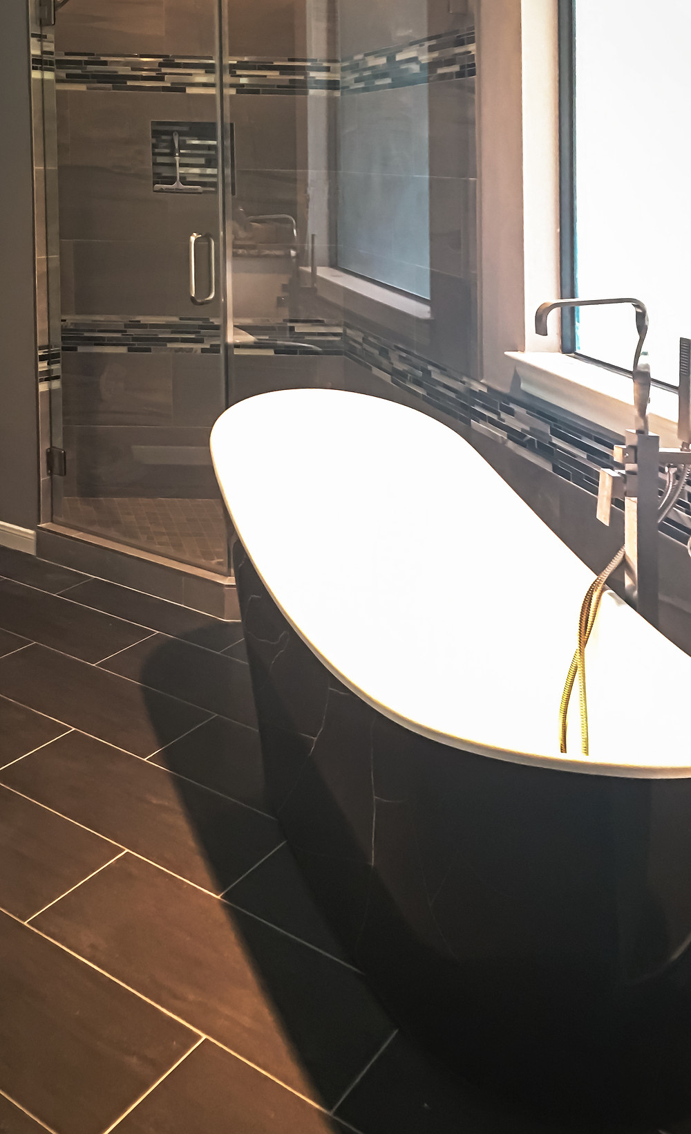 After Picture: Featuring New Black Porcelain Tile Flooring, Glossy Black Freestanding Bathtub, Gray Brown Porcelain Wall Tile and Gray/White/Black/Silver Mosaic Tiles design by K Lilia Interior Design