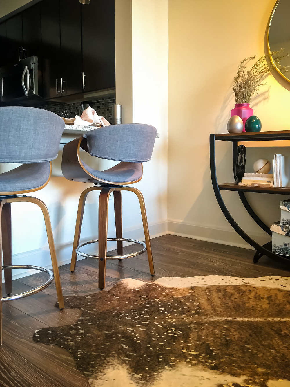 Gray upholstered, walnut wood counter stools, cheetah print animal hide rug, warm wood and black iron console, half-moon mirror