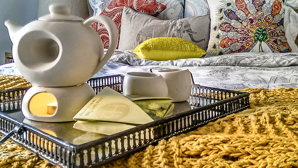 Gray, blue, white damask bedding, yellow throw, Chinese herbal tea, porcelain ivory tealight tea set on a glass top with brown iron base. Various colorful throws on the bed add to the comfort and luxurious feel of this bedroom.