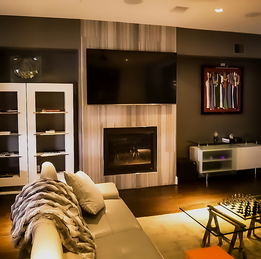 Porcelain gray/brown/tan tiles on fireplace, high-gloss white lacquered bookshelf and media console, leather gray sectional, orange end table, and glass coffee table