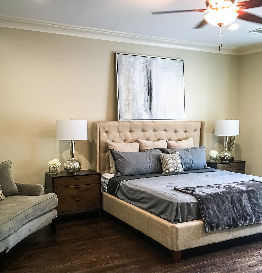 Beige tufted king bed dressed in navy blue and cool blue sheets, and a gray throw blanket. Also, a velvet gray chair-and-a-half with accent pillows sits to the right of the bed. On each side of the bed, exists mocha wood nightstand, adorned by silver table lamps with cotton white lampshades.