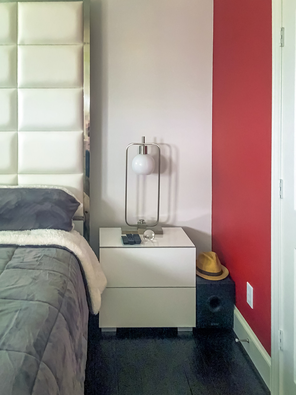 Master bedroom suite with tall, white upholstered bed, gray and white bedding, high-gloss white nightstand, round lampshade with nickel steel base table lamp, and accessorized with small glass globe. This bedroom has dark wood flooring and red accent wall.