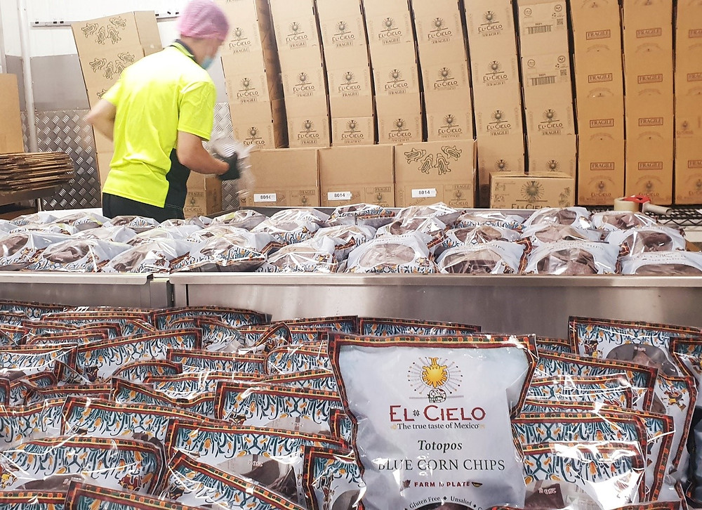 Worker packing El Cielo Mexican food orders into boxes