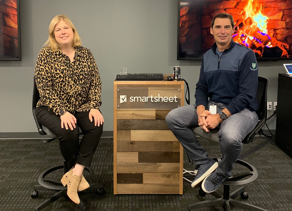 "Amy and Gene are seated facing the camera. Behind them is a podium that has the company name on it, ""Smartsheet"". Behind the podium are 2 televisions that show a fireplace."