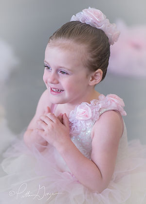 Close-up image of a young dancer in pink ballet costume smiling