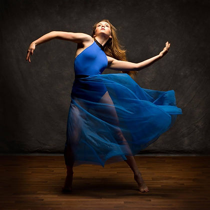 Pre-professional dancer in blue dress with arms curved and lit from above