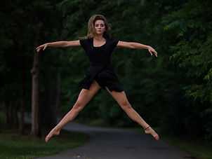 Dancer in a park dressed in black jumping in second position with her arms outstretched.