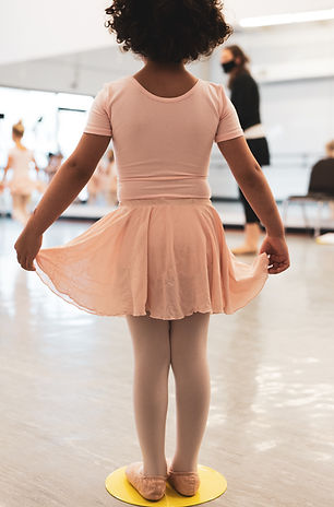 Young dancer in pink holding her skirt with two hands