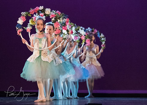 Young dancers in mint tutus holding garlands standing in a line