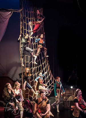 Dancers dressed in pirate gear standing on a net hanging from the stage