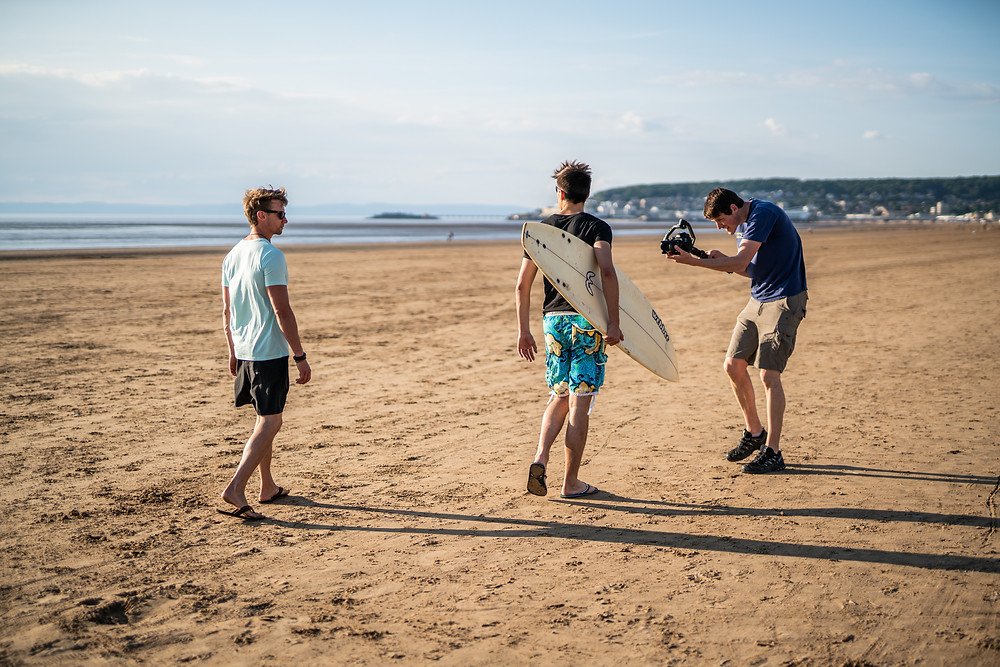 Man films two surfers on a beach - by Havelock, video production in Bristol