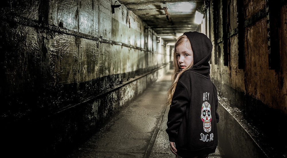 Child in Zero Fox clothing stands in a dirty corridor - by Havelock, Bristol's leading photographers