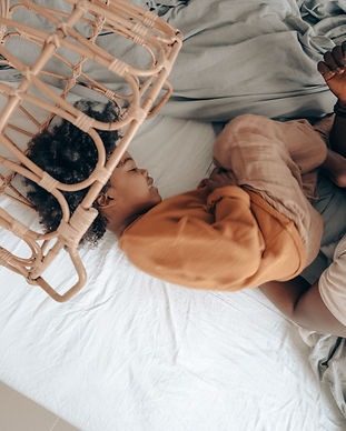 black-kid-playing-with-dad-on-bed-in-lau