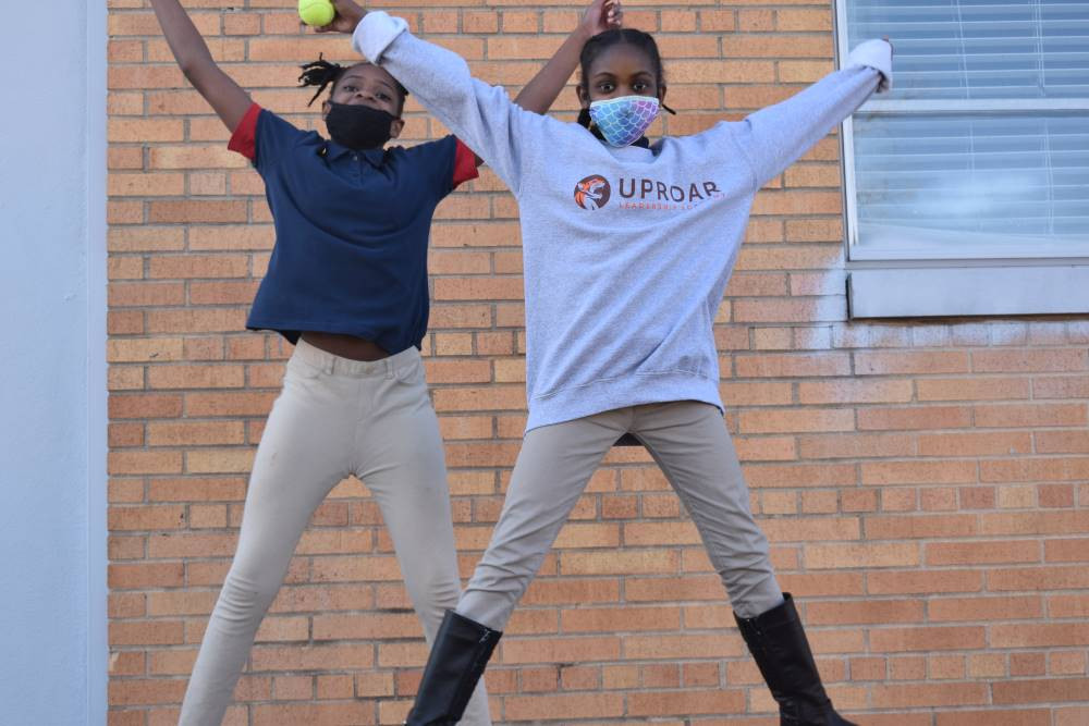 UpROAR Leadership Academy and students in motion with tennis ball
