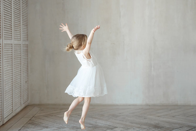 A little girl dancing in a room in a bea